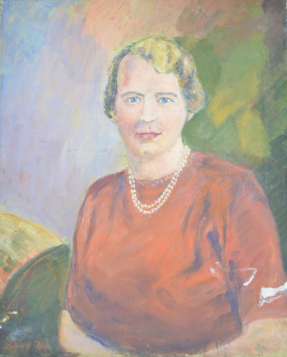 Motivet viser en kvinne med rød overdel og perlekjede som sitter med hendene i fanget. Motivet viser henne fra albuene og opp. Hun har lyst, kort hår og blå øyne. Kroppen er lett dreiet mot venstre, men ansiktet ser rett frem.
