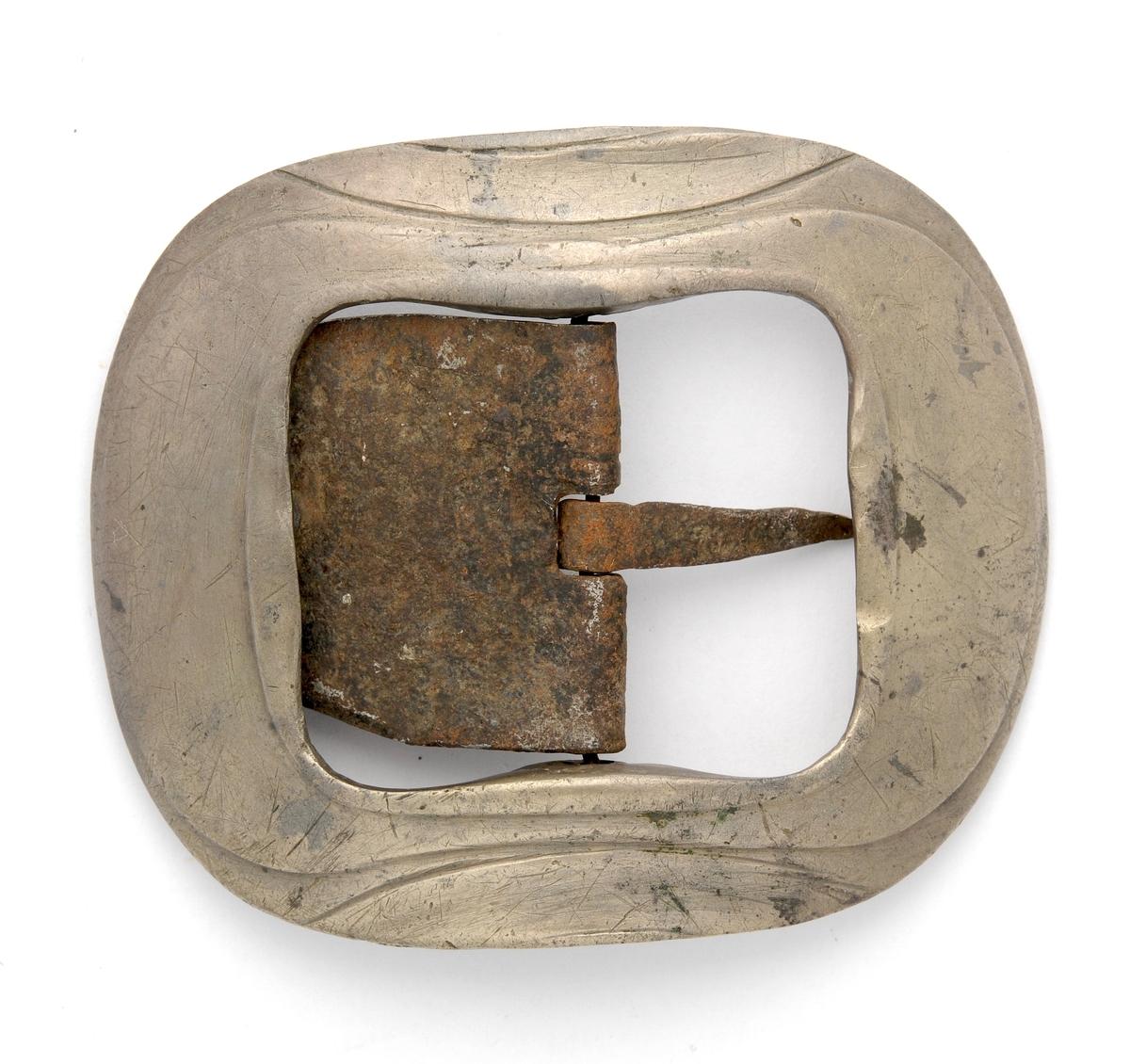 """Skospenne støypt i messing. Tilnærma rektangulær form med avrunda hjørner. Bøygd. Stolpe, kalv og tann smidd i jern. Kalven har ein """"stoppeknapp""""som er nagla på."""