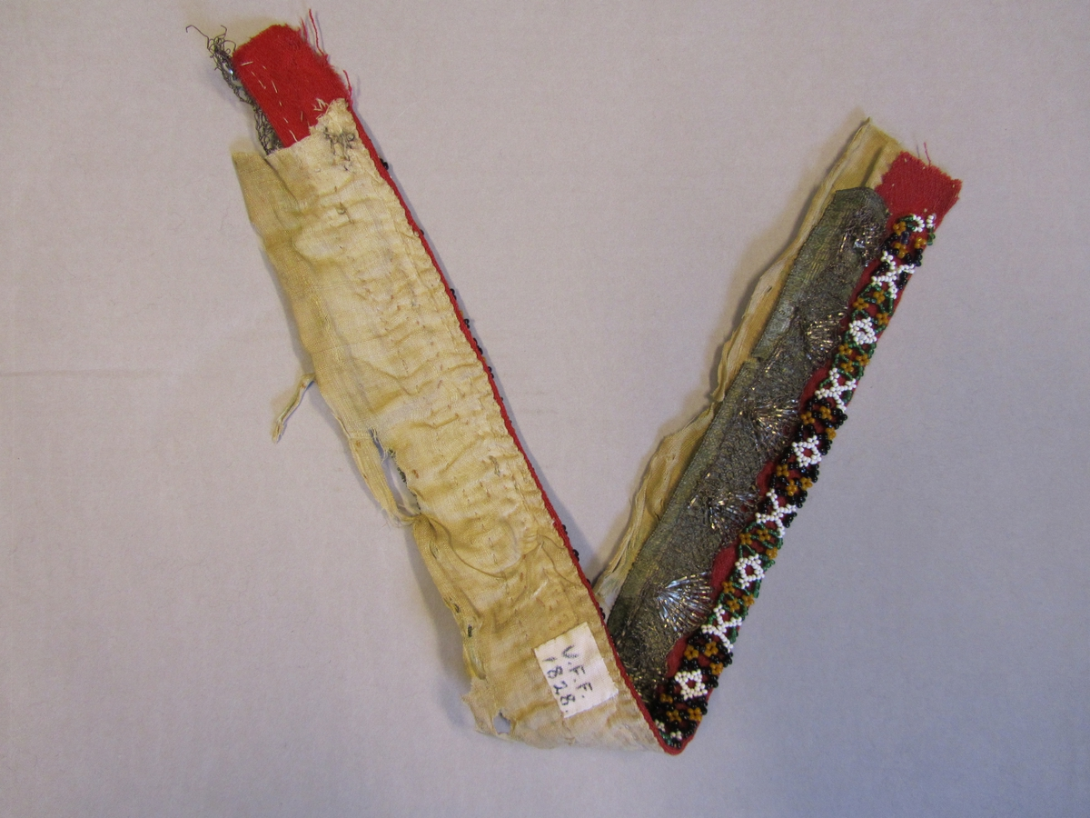 Raudt ull-lerret med sårkantar på tre av sidene. Siste langsida er falda saman med eit dobbeltbretta stoff av tynn linlerrett. Linstoffet er sydd til ullstoffet med faldesting (ser ikkje ut til å vera gjennom på retta).   På ullsida er det påsydd eit perla band og innanfor dette, to metallband utanpå kvarandre. Under dei laust påsette metallbanda er ullstoffet festa til linstoffet med faldesting. Det dobbeltlagde linstoffet fortsett utanfor metallbanda, med bretten i enden av dette.