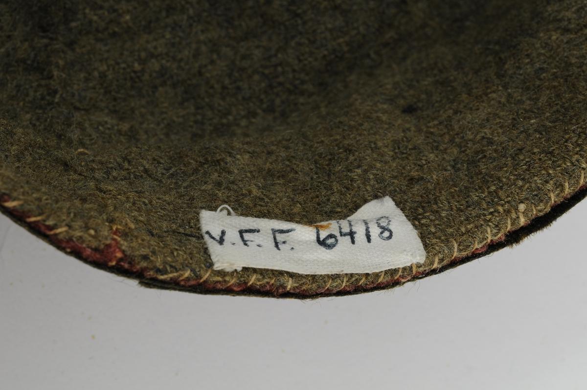 Raud køllelue i ull med svarte (falma, no grønne ) band oppdelt i åtte seksjonar. To rader med band nederst på lua. Fòra med grå/grønn vadmel. Fòret er delt i fire seksjonar.