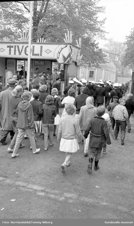 Barnens Dag i Sundsvall. Parad, tivoli och pampig invigning på Stora torge och blåsorkester i Vängåvan där folk njuter i vårsolen. Ett par småkillar passar på att ta en brottningsmatch i all vänskaplighet när invigningen blir för långtråkig.