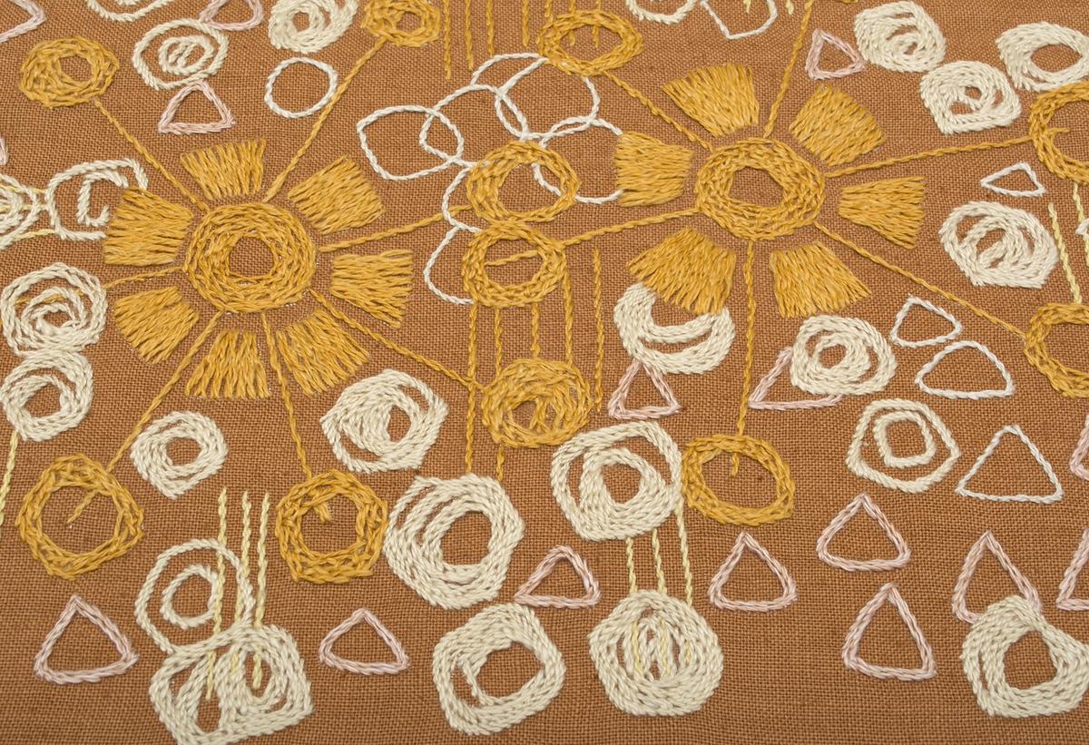 Nästan kvadratisk väska med träbygel och läderrem som handtag. Broderad väska i rostrosa linnetyg, fodrad med halvlinne. Fritt broderi i orange, blekt, rosa, gult i formationen av två blommor och sedan  cirklar och trianglar spridda runt om. Stjälkstygn, schattersöm.