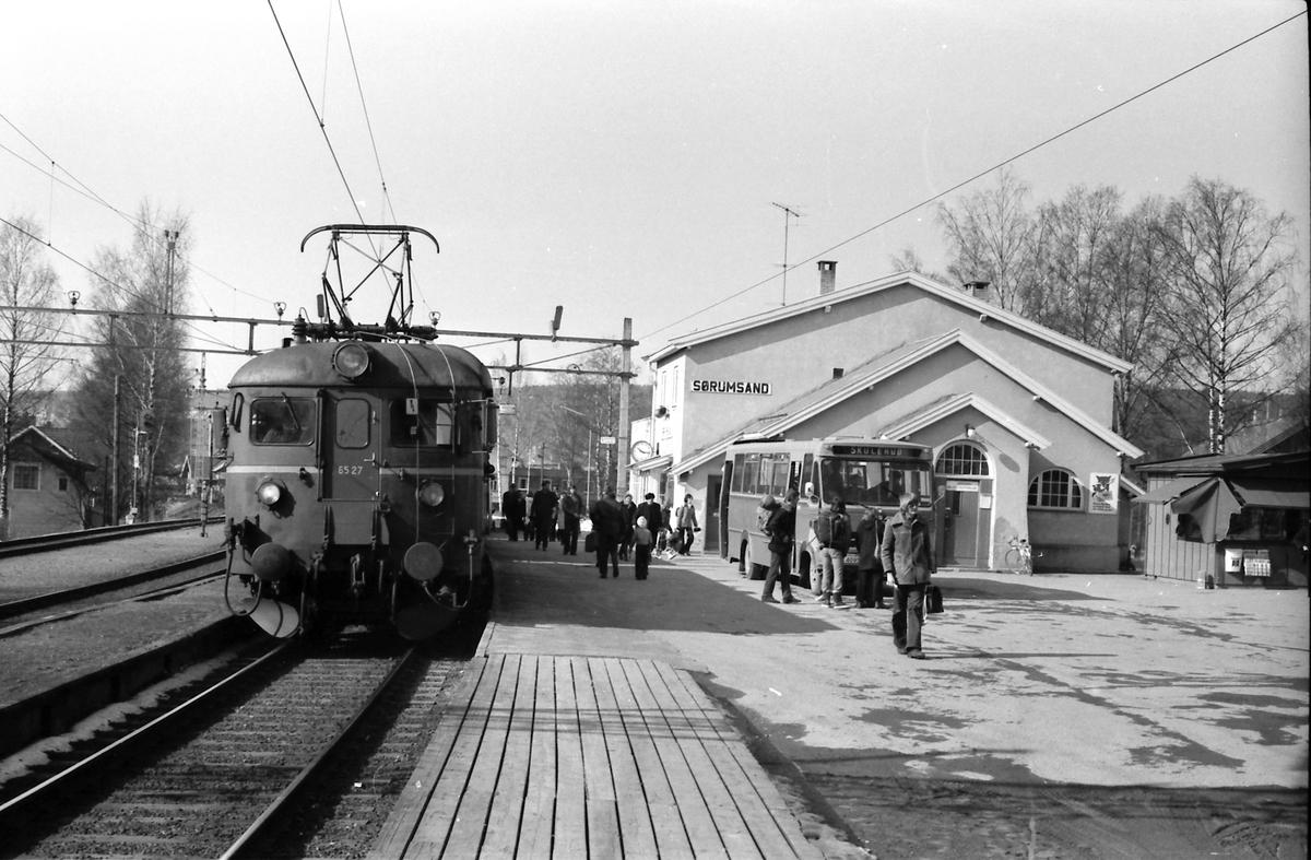 Persontog Oslo Ø - Årnes har stoppet på Sørumsand stasjon. Motorvogn BM 65B 27. Bytte til buss (Hølandsruta) for reisende til Skulerud. Bussen kjørte strekningen til den nedlagte Aurskog-Hølandbanen (Urskog-Hølandsbanen).