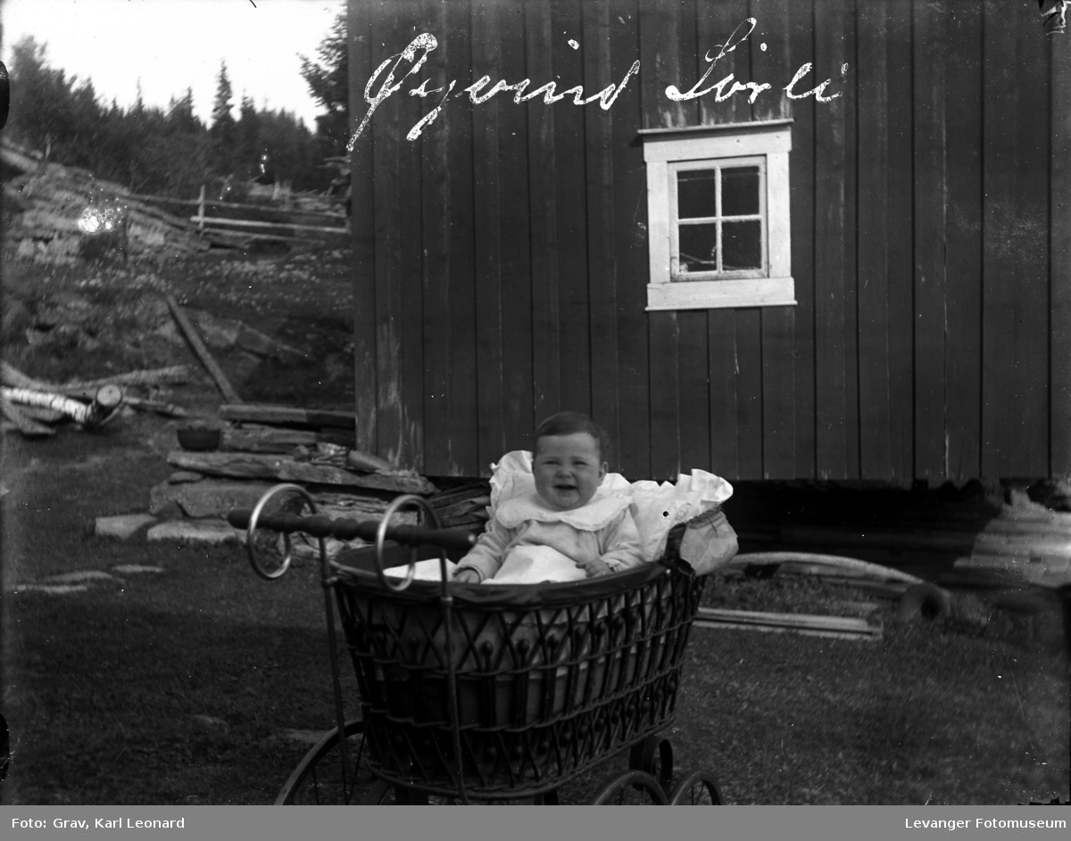 Barn i barnnevogn ute ved et hus Navnet står på bildet