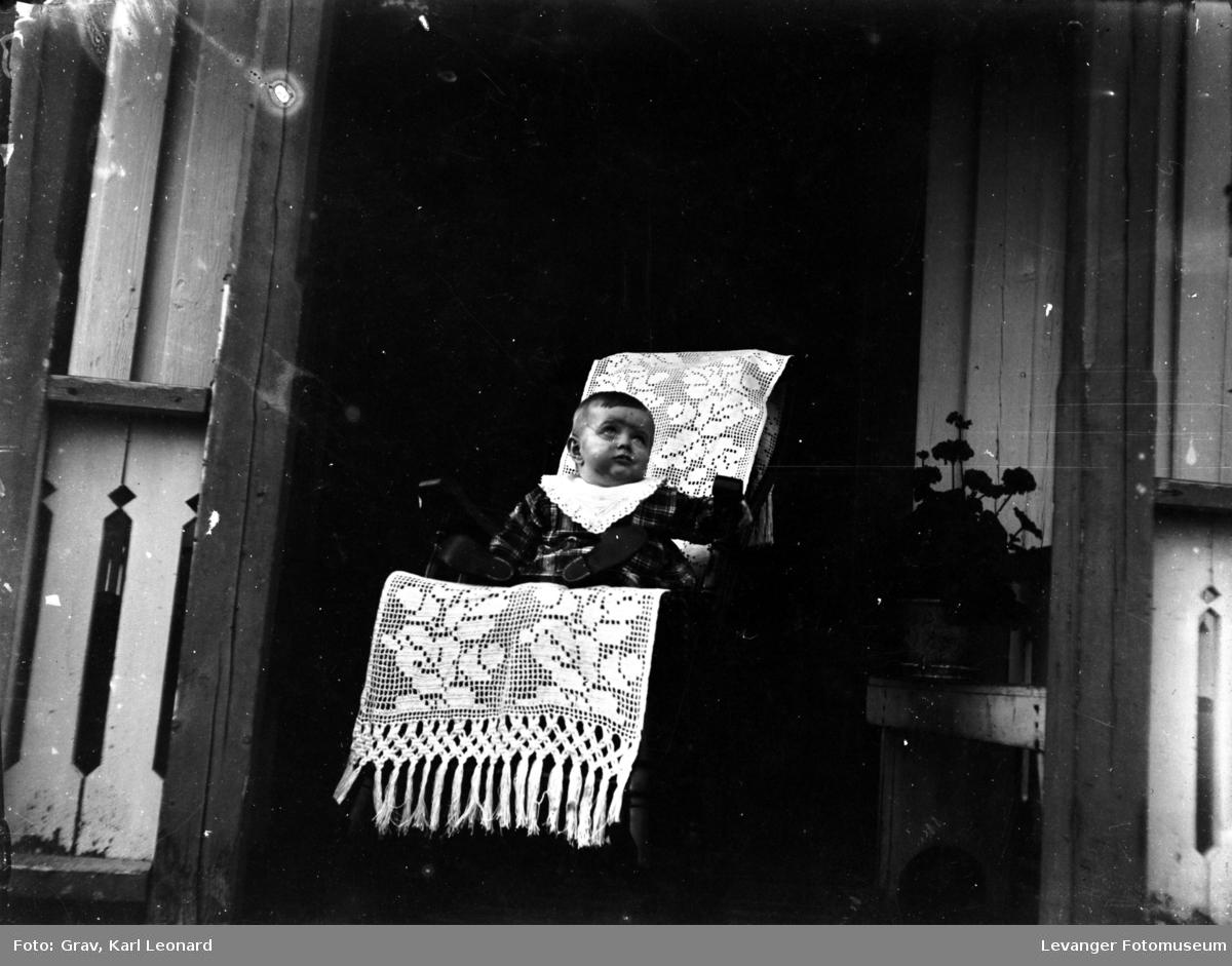 Portrett, barn i stol på veranda