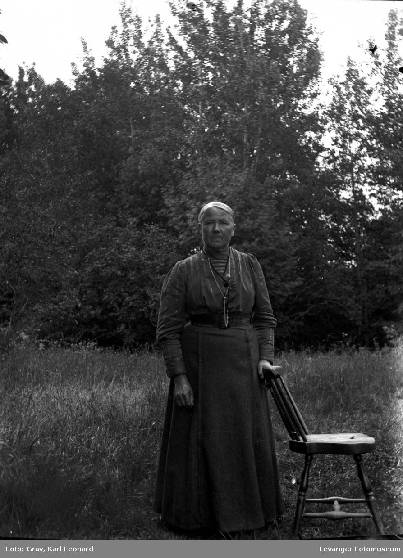 Portrett, kvinne med stol, ute.