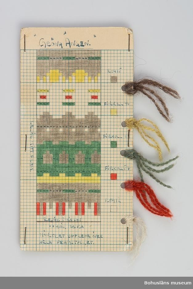 Avlång handtillverkad mönsterritning för mönstret Gröna ängen av Anna-Lisa Mannheimer Lunn från Bohus Stickning. Mönstret är uppritat i bläck och färglagd med pastell- eller vaxkrita på blårutat millimeterpapper, uppklistrat på linneväv och därefter pappkartong. Mönstret skyddas av ett plastskikt fästat med häftklamrar. Utmed högersidan hål gjorda med hålslag med mönstrets olika garner fästade med uppgift om kvalitet/sort och färgnummer. Stämplat BOHUS STICKNING på baksidan.