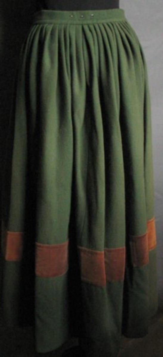 Knäppa, grönt ylletyg med brett brunt sammetsband nertill, sprund åt vänster, slätt parti mitt fram, lagda veck över höfterna och baktill. Sydd av tre våder tyg. Bredd nertill 1250 mm. Sammetsbandet 95 mm brett 245 mm från nederkanten. Skoningen 58 mm bred. Linningen 36 mm bred med två par hyskor/hakar och två par tryckknappar som stänganordning. Sprundet (mätt från under linningen) 200 mm med tre par hyskor/hakar är fodrat med linnetyg. Tre hyskor bak på linningens utsida för knäppning med livstycke, 25 mm mellan varje. Upphängningsöglor i dubbelvikt blått bomullsband placerade över höfterna.