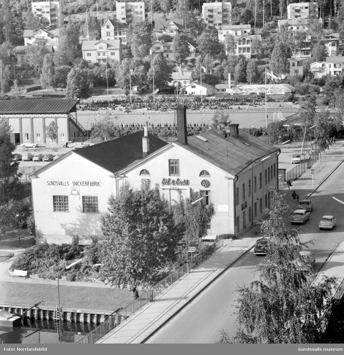 Sundsvalls Snickerifabrik och Bil & Buss invid Selångersån vid Storbron och i bakgrunden Idrottsparken där det pågår en fotbollsmatch.