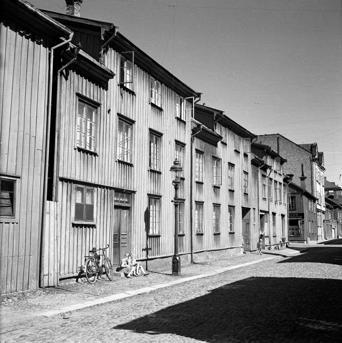 En kullerstensgata i Jönköping. Två flickor sitter på trappan till ett bostadshus av trä. En cykel står lutad mot väggen. Den gamla Jönköpingslyktan vid vägkanten gav inte mycket ljus om natten. Längre ner på gatan ligger en affär med hattar i skyltfönstret.