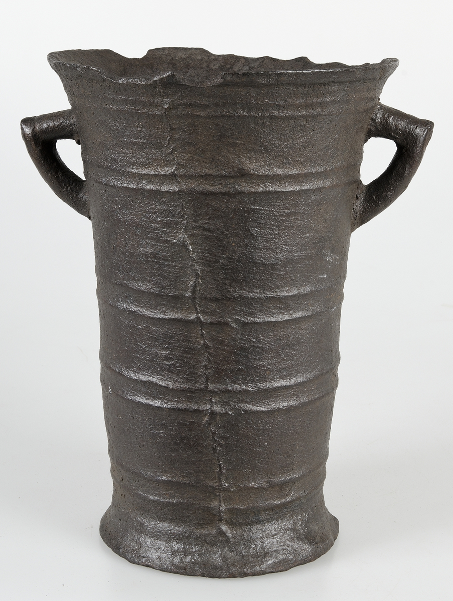 """Bultlås av järn med svaga rester av förkoppring. Två """"gördlar"""" kring kolven, en smalare, som omsluter hela kolven, och en bredare med vikta ändar. Dessa har rader med punkter och halvcirkelformade instansade ornament."""