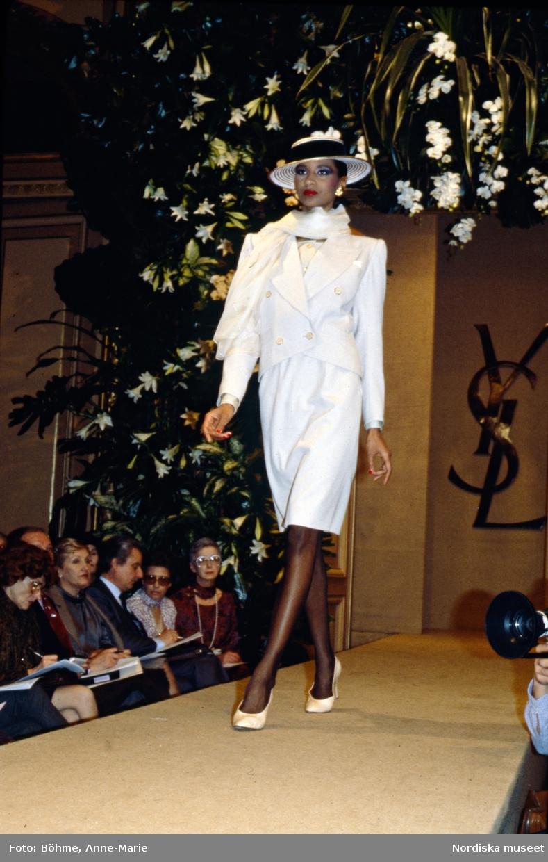 Modevisning. Modell i vit klänning, kavaj, sjal och hatt med hattband. Från Yves Saint Laurent.