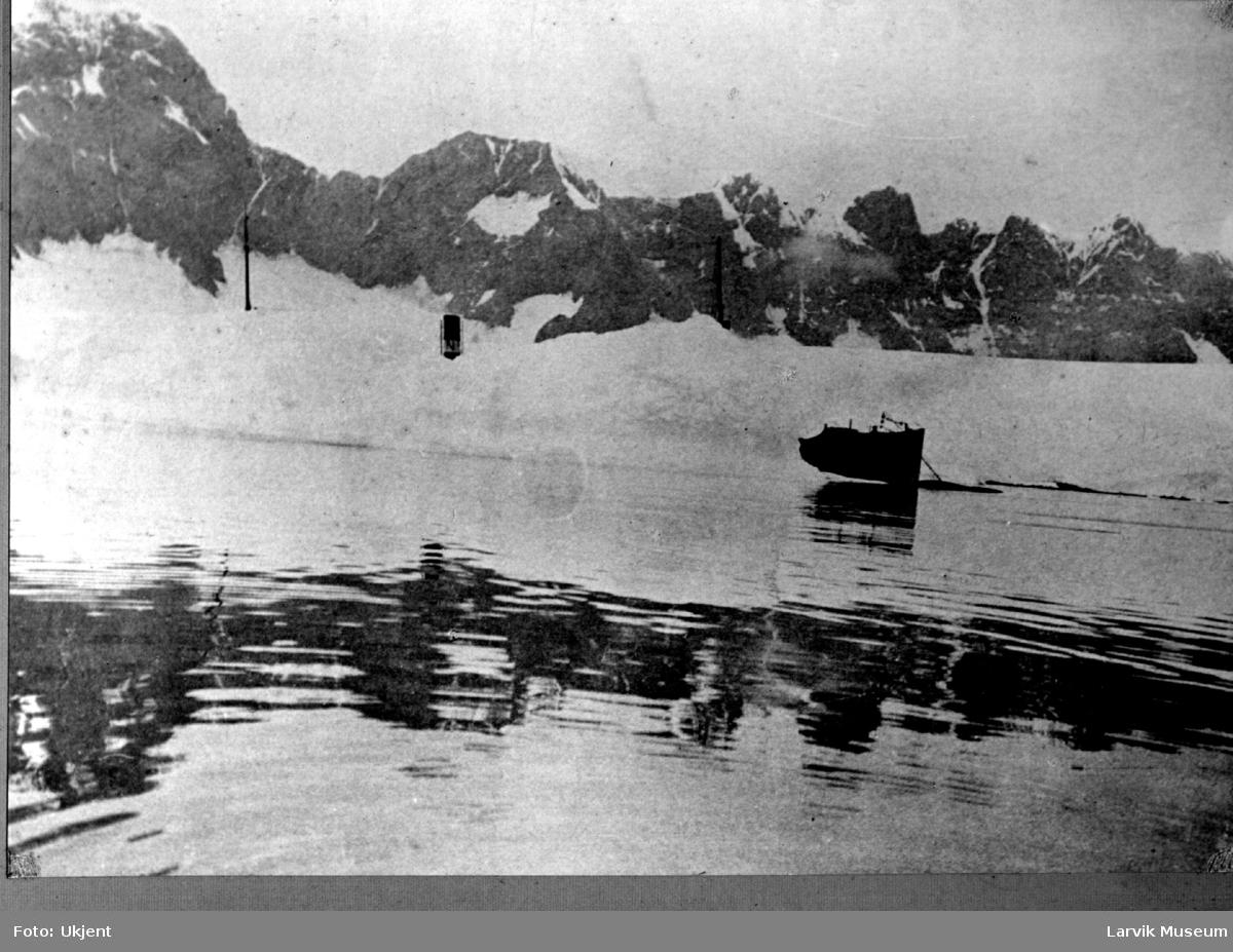 """Hvalkokeriet """"Solstreif"""" på fangststasjonen, delvis skjult av isen. Litt av baugen, skorsteinen og mastene stikker frem."""