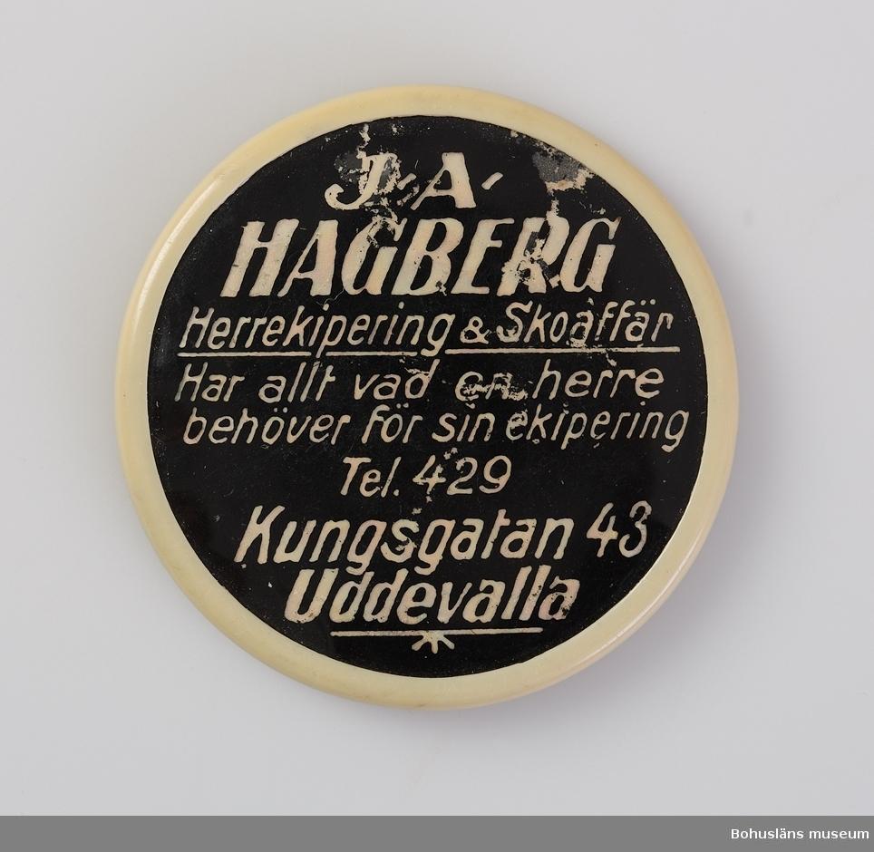 Rund reklamspegel med baksida av svart plast och påtryck i vitt: J-A HAGBERG Herrekipering & Skoaffär har allt vad en herre behöver för sin ekipering Tel. 429 Kungsgatan 43 Uddevalla