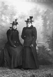 Två kvinnor i tvådelad dräkt med dubbelknäppt jacka 3700b77d0c07c