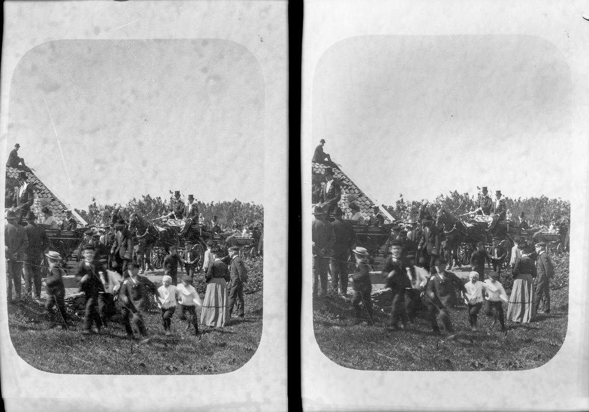 Samling på Haraldshaugen. Barn i forgrunnen. Mange personer, kvinner og menn. Trehus til venstre, hvor det sitter en mann på taket. To hester midt på bildet, som trekker en kjerre. I denne og på hestene sitter det menn med flosshatter. Noen få andre hester/kjerrer og trær i bakgrunnen.