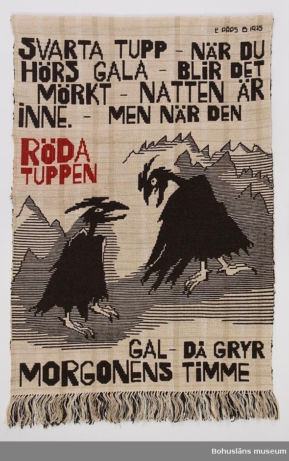 """Finnväv, mönstrad dubbelväv med svart och röd bild och text mot vit botten. Två svarta tuppar vända mot varann mot en bakgrund av bergslandskap.  I versaler svart och  röd text ovan och under motivet: SVARTA TUPP - NÄR DU  HÖRS GALA - BLIR DET MÖRKT - NATTEN ÄR INNE. - MEN NÄR DEN RÖDA TUPPEN GAL - DÅ GRYR MORGONENS TIMME  I övre högra hörnet signerad """"E PÄRS B 1975"""" Vävnaden avslutas med en frans. Montering: Kanal upptill med träkäpp inuti. Ögleskruvar i käppens ändar."""