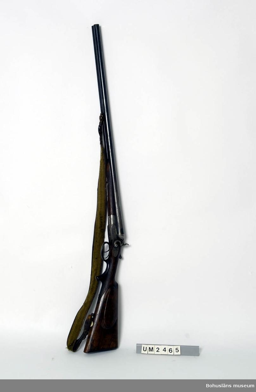 """Ur handskrivna katalogen 1957-1958: Tvåpipigt jaktgevär 117 cm längd Tillverkare: W.W. Greener, Birmingham, """"42525""""; träkolv m. skydd f. avtryckare av horn. Axelband i läder o tyg.  Lappkatalog: 55"""