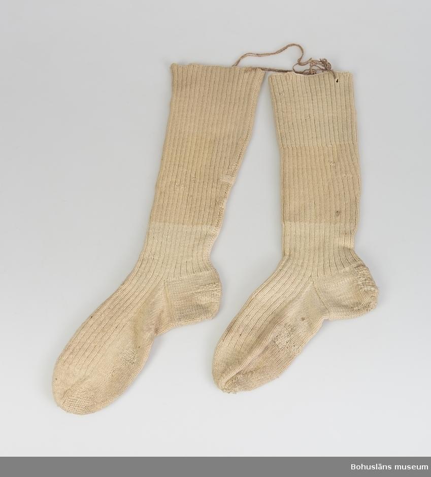 Ofärgade yllestrumpor. Foten nystickad och påsatt skaften. Stoppad på såväl fot som skaft. Personuppgifter, se UM020945.