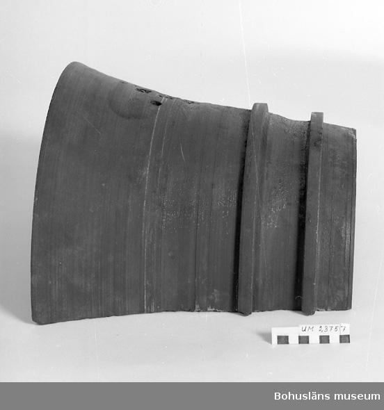 Funktion: Vid inpressning av bandet. Klockformad på insidan två stycken 1,5 cm fyrkantiga skåror, på utsidan försedd med motsvarande förstärkning. Hål för fastsättning med diameter 1 cm. Bitar avslagna ur ena hörnet. Uddevalla Tunnfabrik flyttade 1957 till Källviken, Dragsmarks socken och kallades Källvikens tunnfabrik.