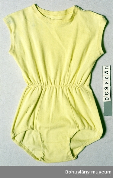 """Ljusgul gymnastikdräkt av bomullstrikå. Ärmlös och benlös. Resårband invändigt i midjan och i kanaler vid benringningarna. Rundringad i halsen. Halsen och armhålen kantade med muddväv. Öppning på ena axeln, knäpps med fyra pärlemorknappar, varav en saknas. Etikett i höger sida på insidan med texten: """"WESTERHOLMS 38"""". I etiketten är ett bomullsband med handskriven text fastsytt:  """"AGNETA WALLIN 8 A LUNDBY SAM"""".  Brukaren är S o O Anderssons dotter Vivianne Andersson f. 1942. Använd på Flickskolan på 1950-talet. Blå-gröna fläckar upptill fram."""