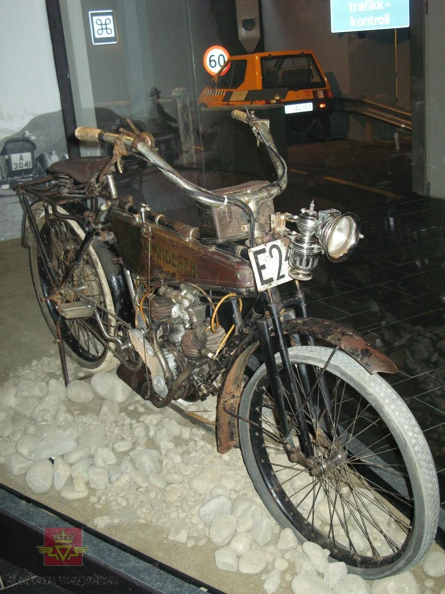 Tohjuls motorsykkel, svart og grønn med staffering og merking i rødt. Motorsykkelen har en 2-sylindret bensindrevet V-twin motor med sylindervolum 404 cm3 og en ytelse på 3,5 hk.. Merking fra produsent. Har utdatert kjennemerke festet til sykkelen.