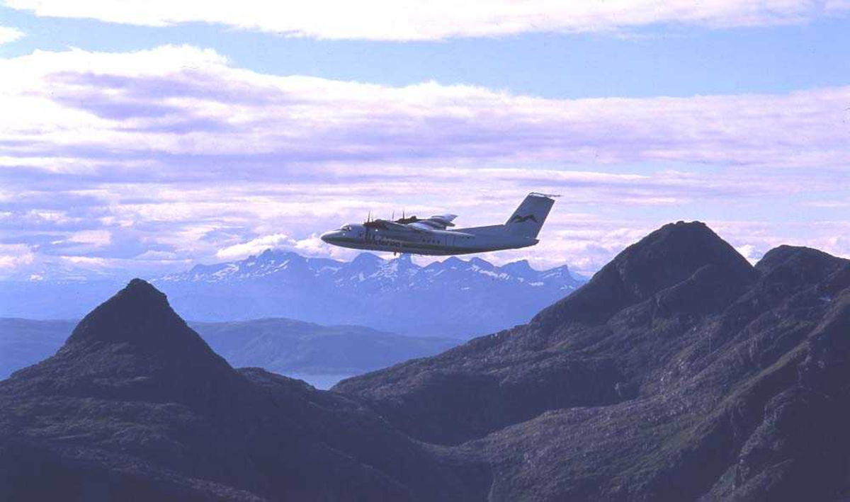 Luftfoto. Ett fly, LN-WFK, DHC-7-102 / Dash7 fra Widerøe passerer over Landegode utenfor Bodø. I bakgrunnen ses fjellkjeden Børvasstindane.