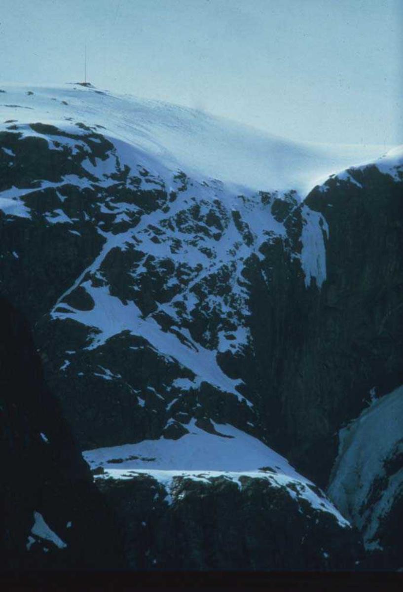 Landskap. Majestetisk fjelltopp ikledd vinterskrud. På toppen ses et antennesystem.