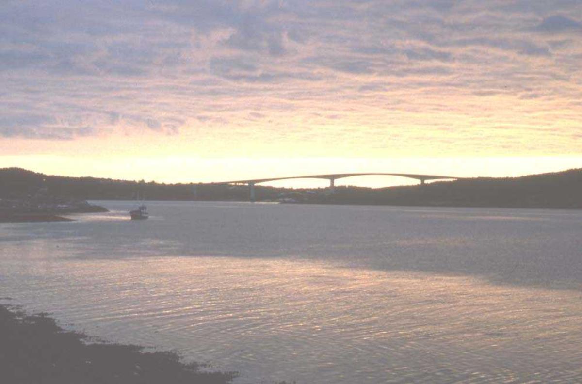 Landskap. Kveldsol. I horisonten skimtes en bro som binder to øysamfunn sammen.