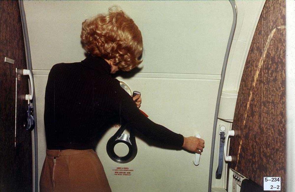 En person som åpner/lukker en dør på et fly, Boeing 737-200.