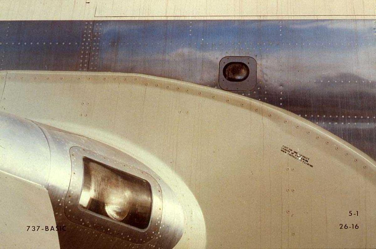 Detaljbilde av to lys ved vingen på ett fly, Boeing 737-200.