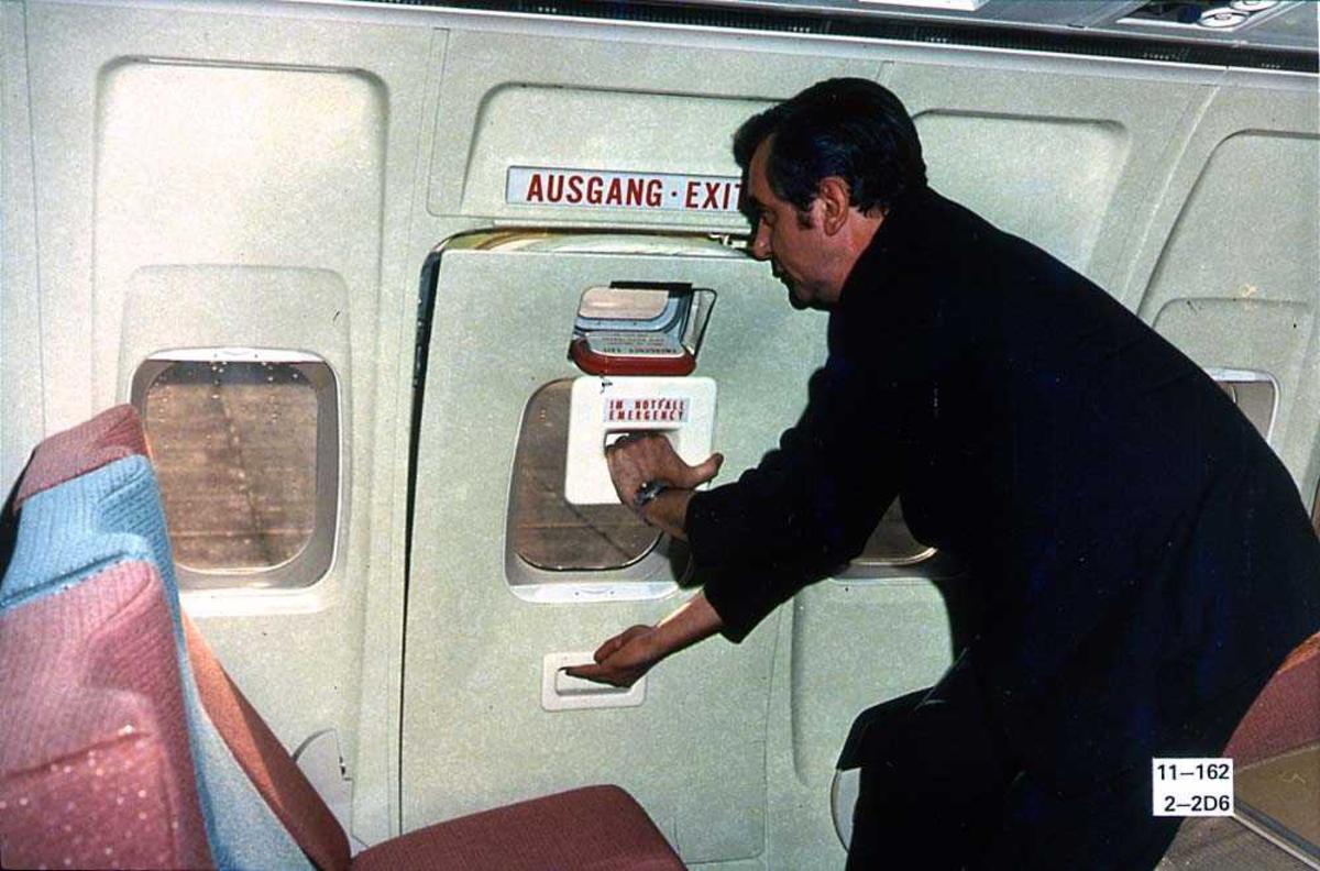 En person inne i kabinen på ett fly, Boeing 737-200, som åpner nødutgangen.