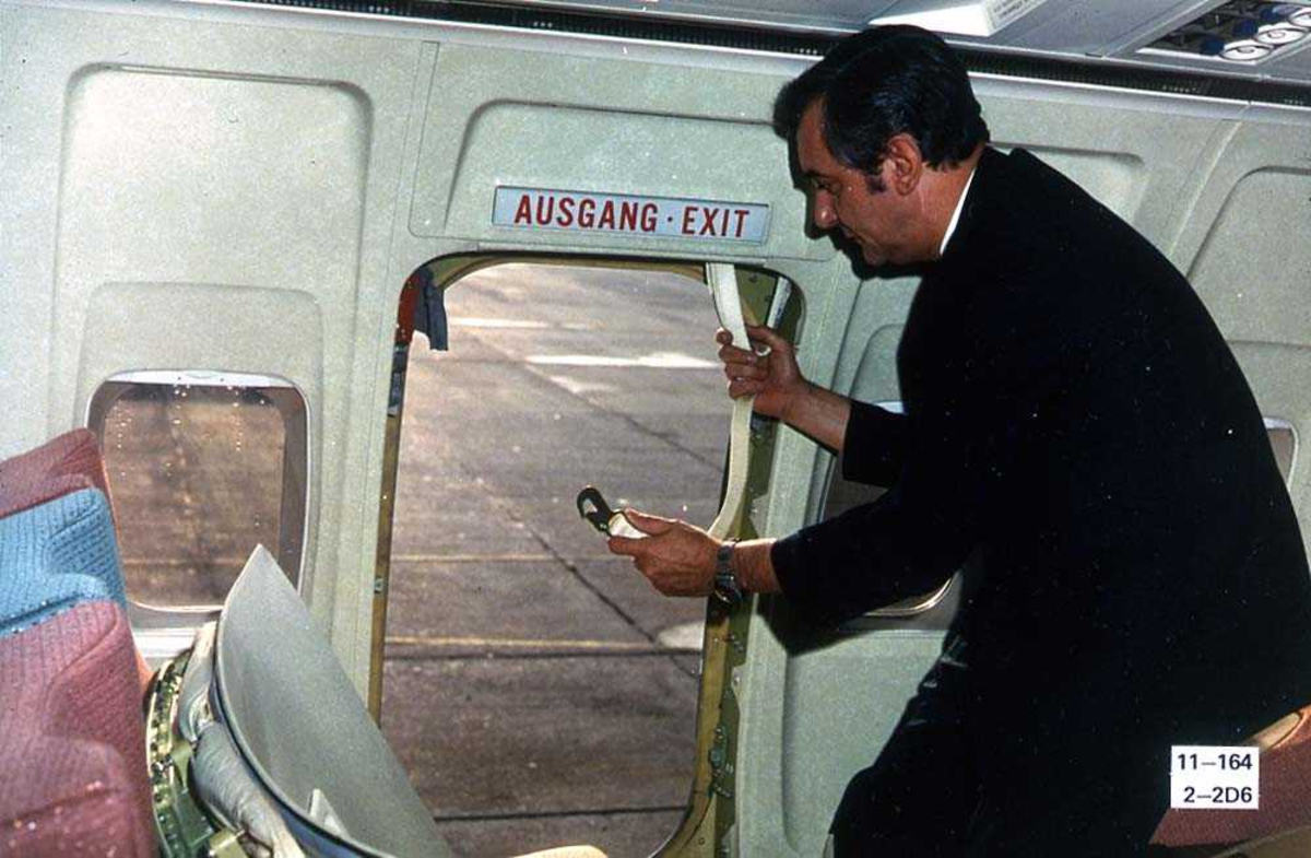 En person inne i kabinen i ett fly, Boeing 737-200, ved nødutgangen.