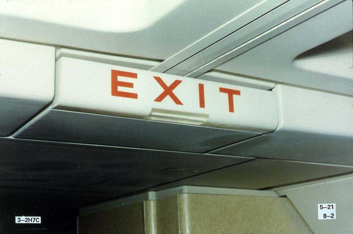 Detaljbilde av et exit-skilt inne i kabinen på ett fly, Boeing 737-200.