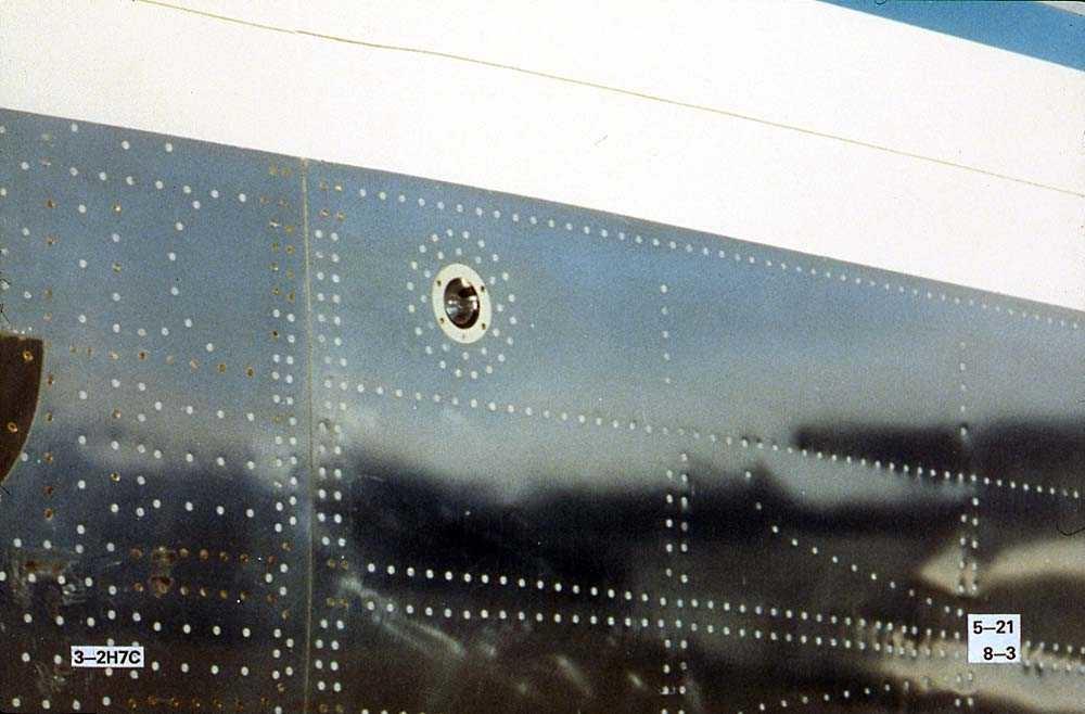 Detaljbilde av skroget på ett fly, Boeing 737-200, med et lys.