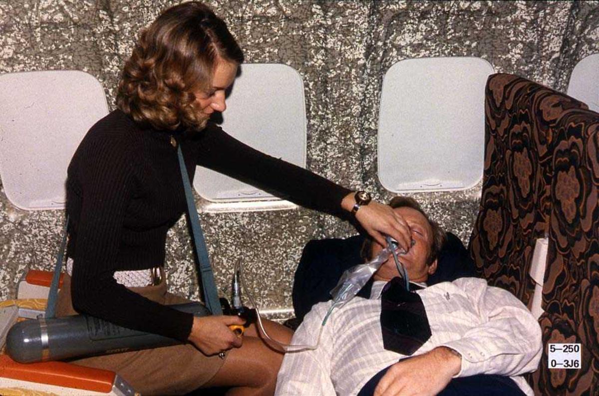 To personer inne i en flykabin på en Boeing 737-200. Den ene personen har en oksygenflaske med en slange som hun holder over nese og munnen på den andre personen.