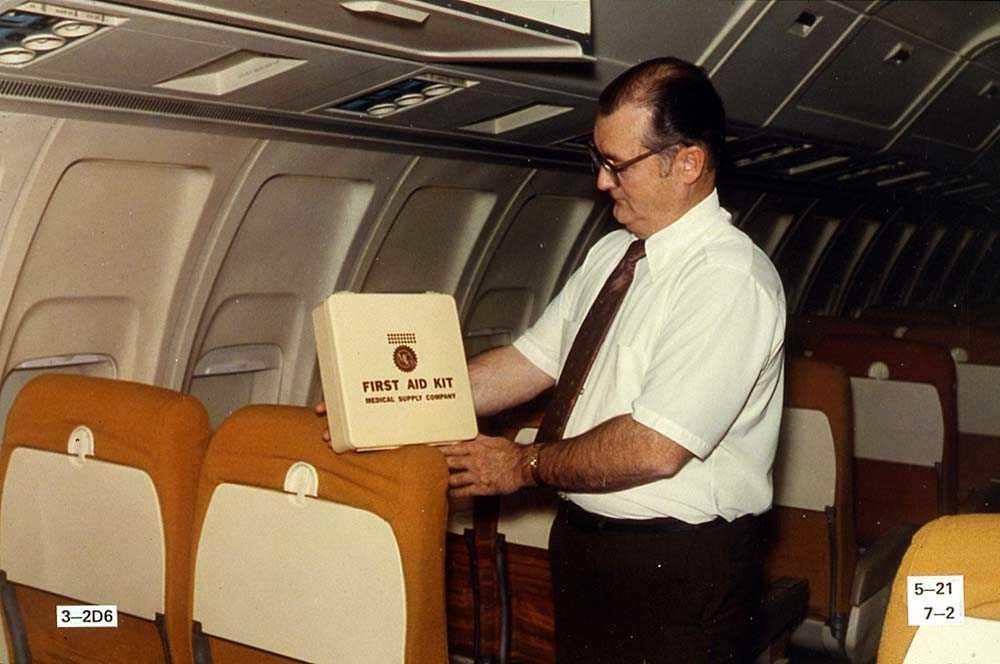 En person som står i kabinen på et fly, Boeing 737-200, og holder i et førstehjelpskrin.