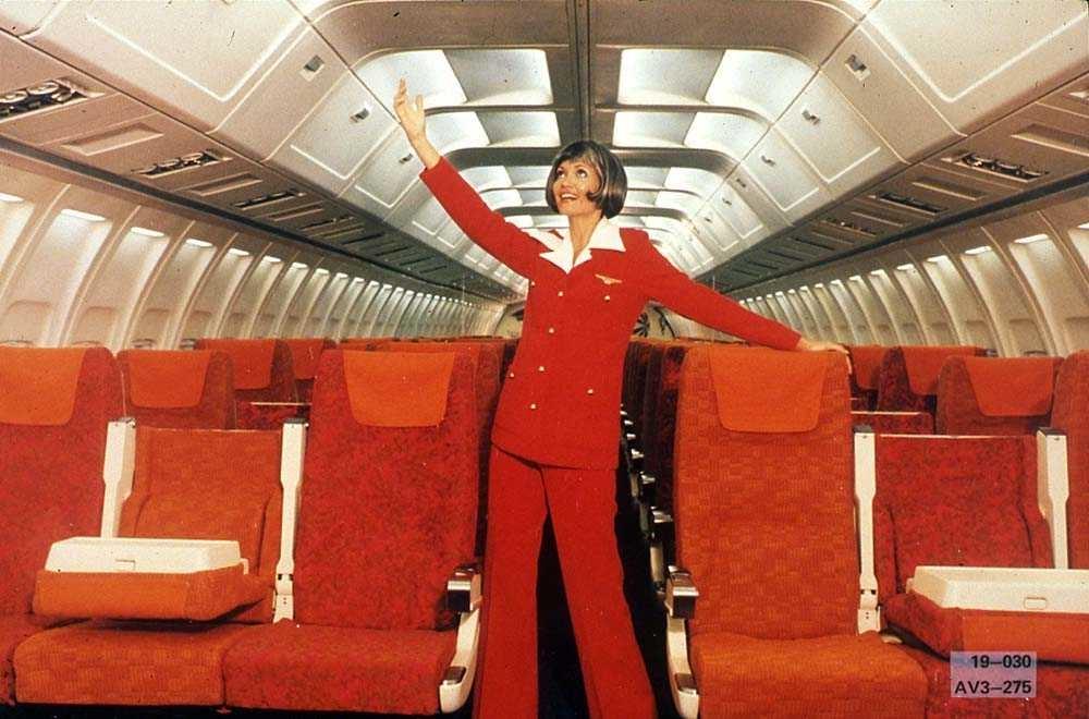En person som står i midtgangen inne i kabinen på ett fly, Boeing 737-200.