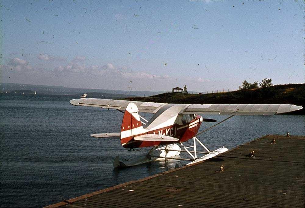 Ett sjøfly som ligger ved en kai, Piper PA-22-160 Tri-Pacer LN-KCI.