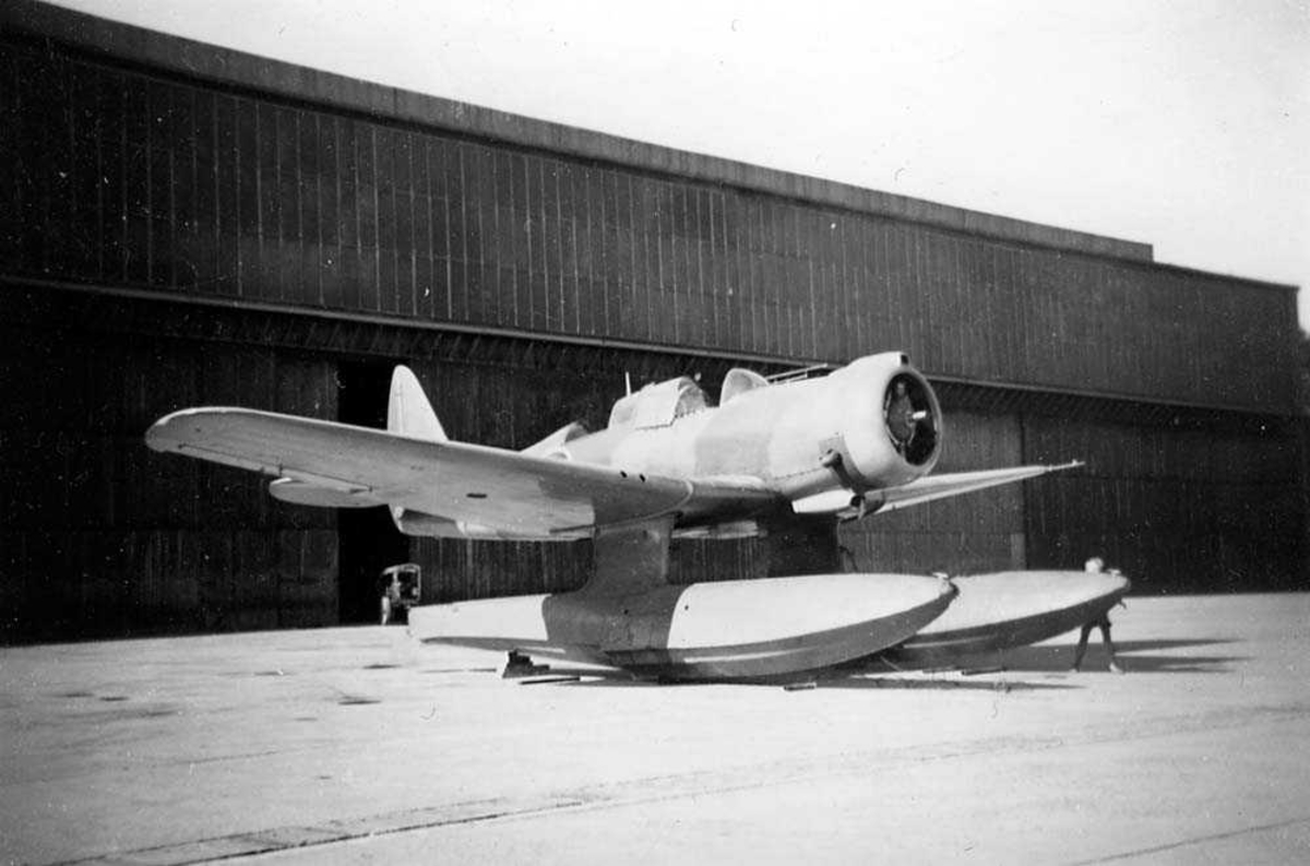 Lufthavn. Ett fly på bakken, Northrop N-3PB med flotører, foran en hangar.