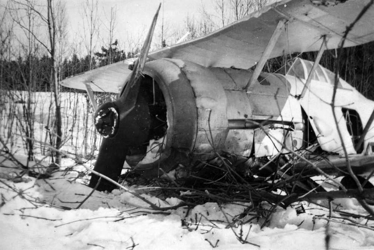 Landskap. Et fly, Gloster Gladiator, har styrtet på en snøkledd slette med kjerr. Flyet har fått betydelige skader.