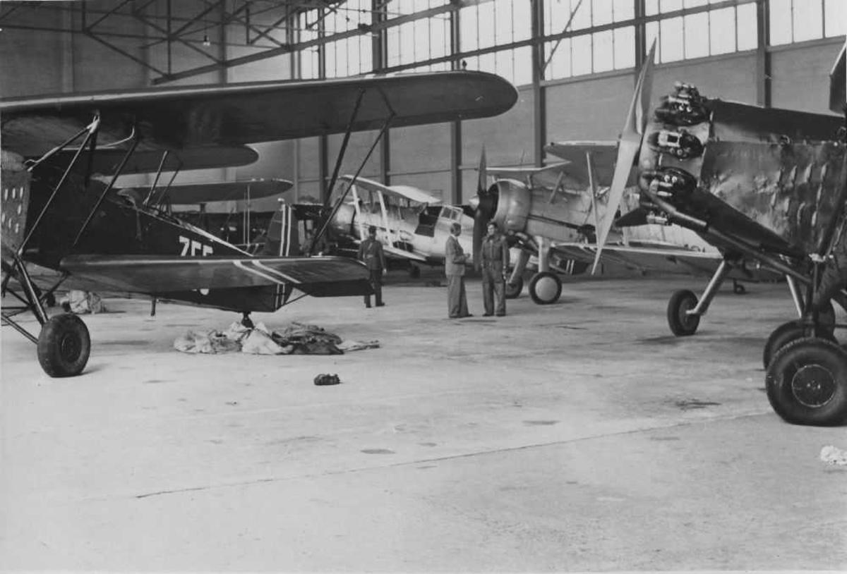 Landskap. Hangar. Tre personer vandrer rundt en samling med fly. Disse er sannsynligvis inne til ettersyn.