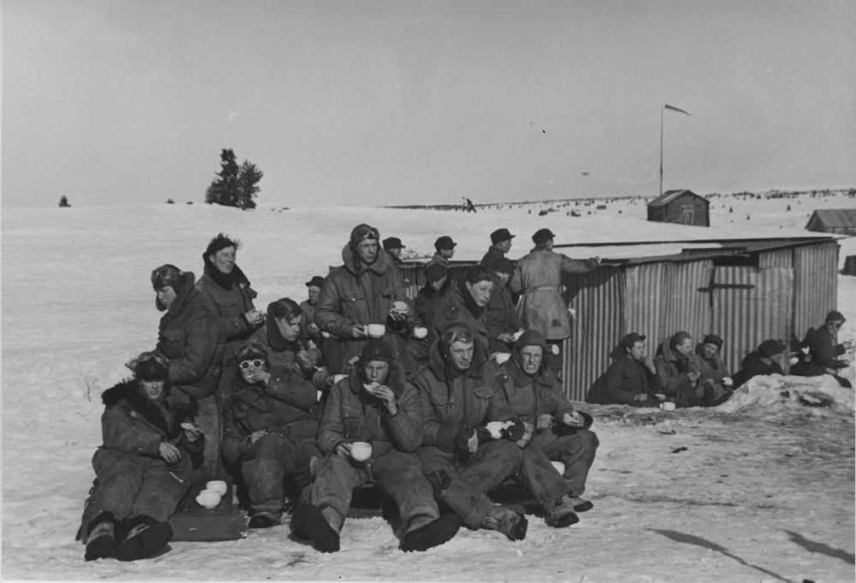 Landskap. En gruppe uniformerte personer har pause og koser seg ute i solskinnet og snøen. En liten bygning i bakgrunnen med en vindpølse som indikerer vindretningen.