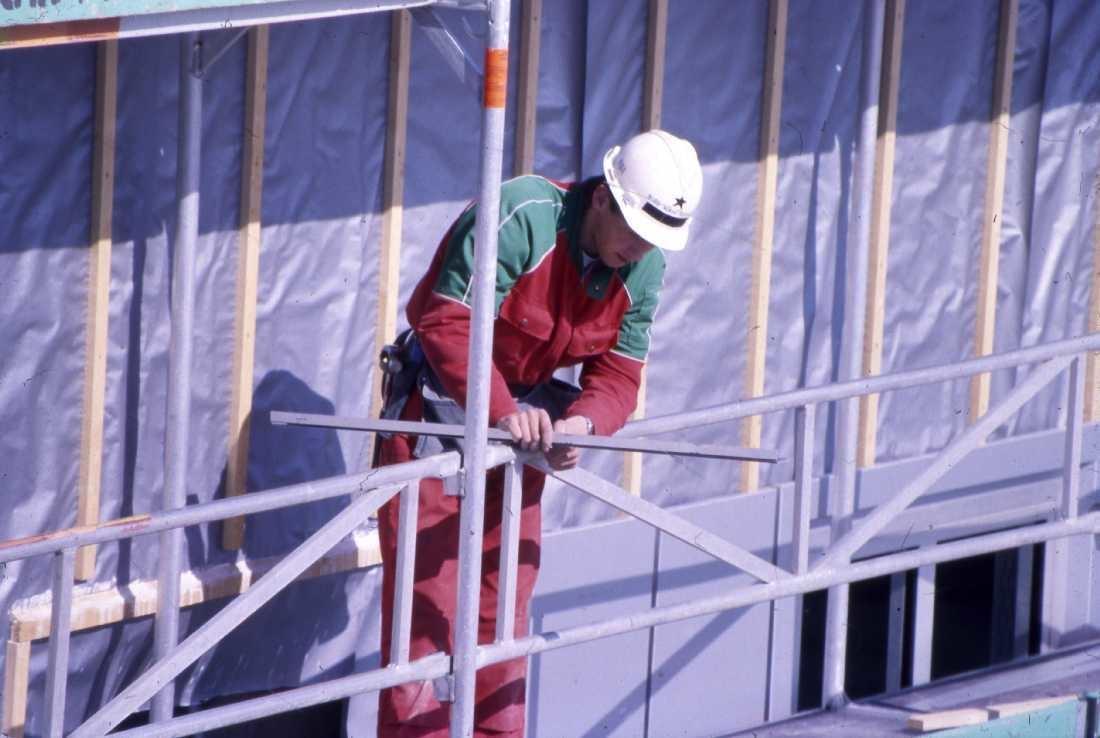 Lufthavn - flyplass. En person på stillas i aktivitet med legging av fasadeplater.