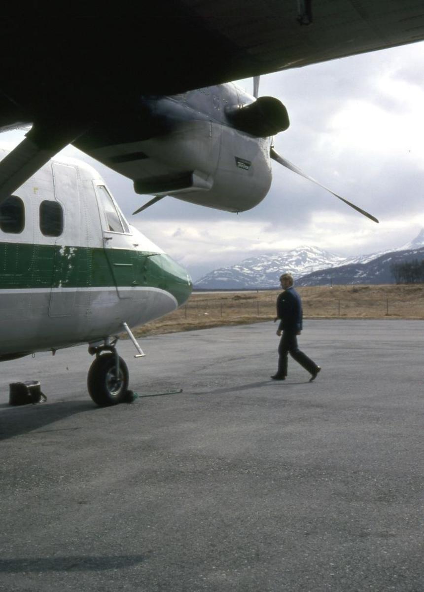 Lufthavn (flyplass). Et fly, LN-WFC, DHC-6-300 Twin Otter fra Widerøe klar for oppstart. En person (lufthavnbetjent) foran flyet.