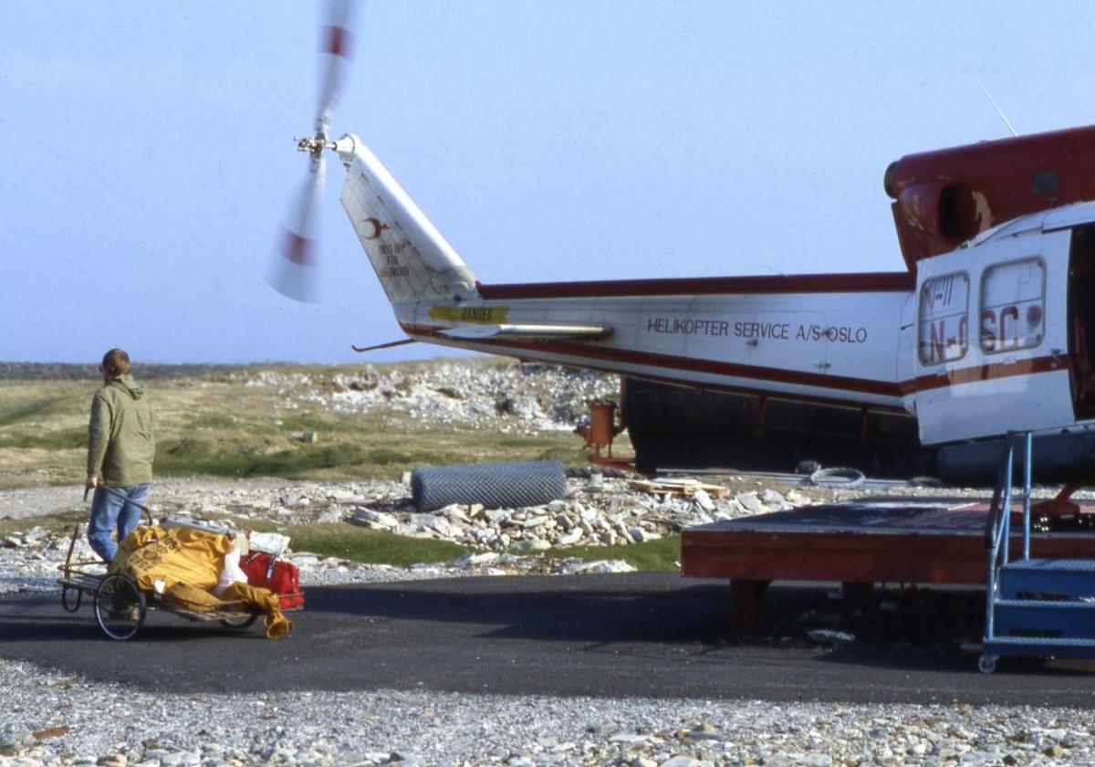 Lufthavn (heliport).  Et helikopter, LN-OSC, Bell 212 fra Helikopter Service parkert på heliporten.. En person med bagasjevogn.. Opererer Widerøe rute.