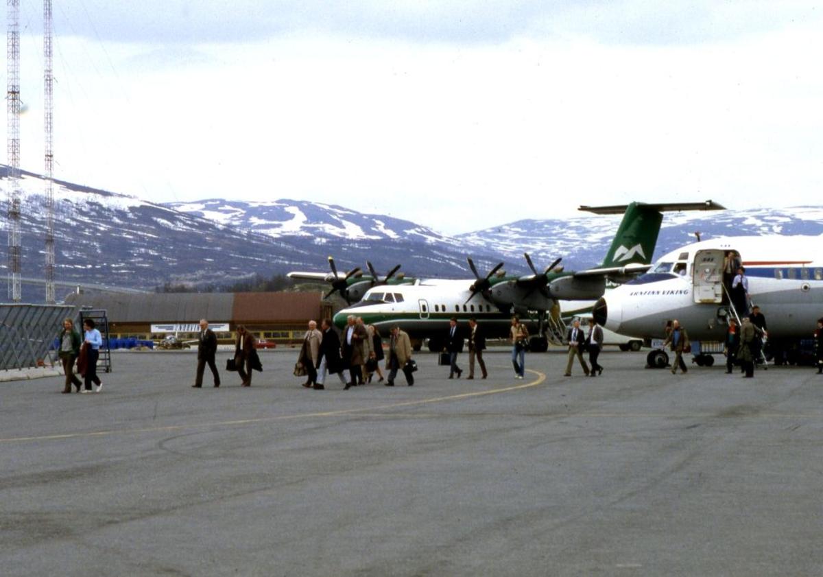 Lufthavn (flyplass). To fly, DHC-7-201 Dash 7 fra Widerøe og en DC9 fra SAS parkert. Passasjerer forlater SAS flyet på vei mot flyterminalen. I bakgrunn skimtes Norving hangar.
