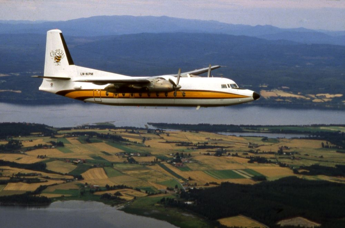 Luftfoto. Et fly, Fokker F.27 Friendship fra Busy Bee underveis til neste stopp. Flott utsikt til bakken under oss.