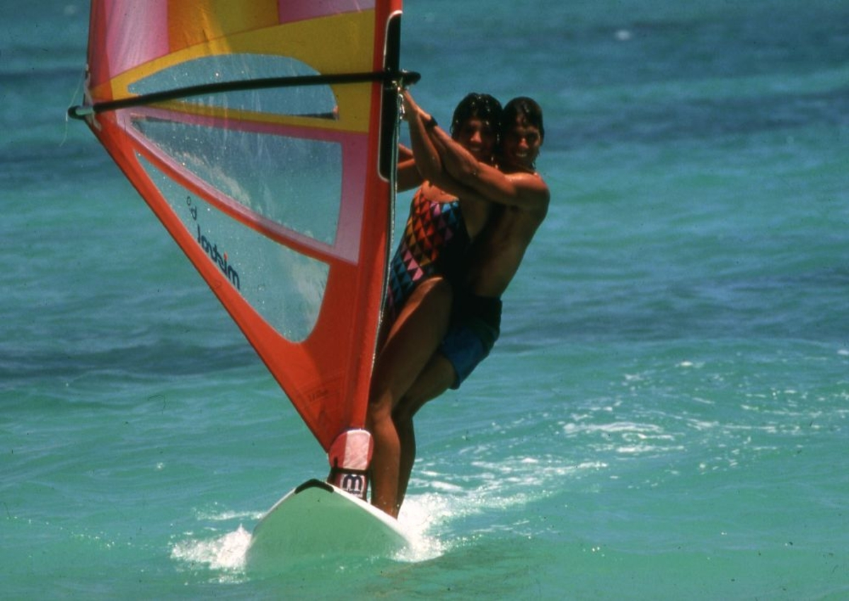 Landskap. Turistparadis. To personer vindsurfer i behagelige omgivelser under ferieoppholdet.