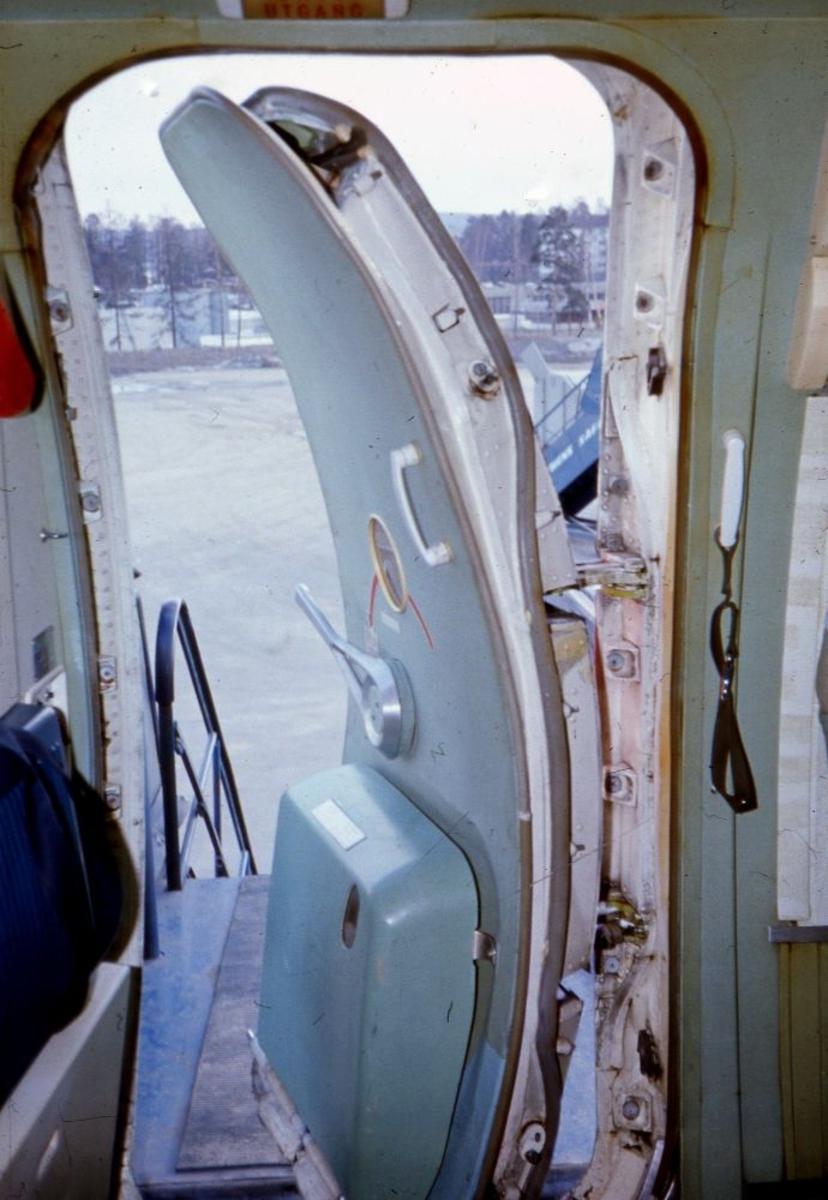 """Lufthavn/Flyplass. Nærbilde av """"airstairdoor"""", passasjerdør med tilhørende trapp sett fra innsiden til et fly fra Braathens SAFE."""